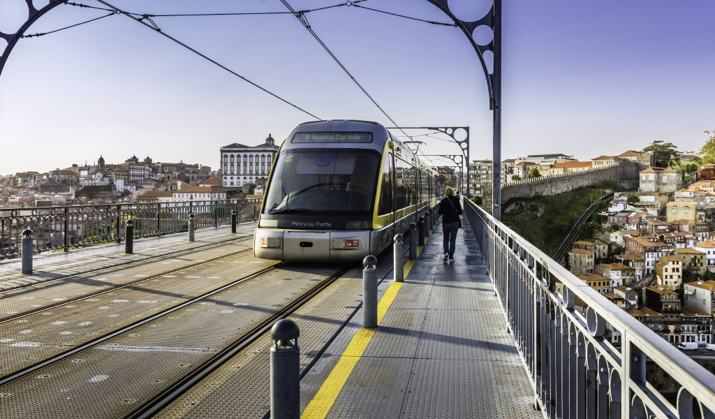 Porto, Portugal - May 22, 2016: Metro rail seen from the front travelling over the Dom Luis I bridge that lies over river Douro in Porto city. This is a popular tourist destination declared a UNESCO world heritage site. The cityscape seen on either side of the bridge.